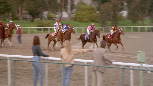 medium angle pan right of horse race starting gate. seven horses with jockeys leave gate approaching right as race starts. gate has sign reading hollywood park. people leaning over fence to watch race. - starting gate stock videos and b-roll footage