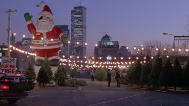 medium angle of giant inflatable santa claus  on left with sign reading santa's christmas tree parking.  see world trade center in far background. christmas tree lot on right. lines of horizontal christmas lights above trees. - christmas tree stock videos & royalty-free footage