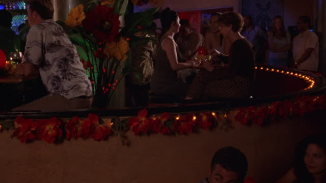 MEDIUM ANGLE OF PEOPLE DRINKING AND SOCIALIZING IN RAISED, CROWDED BAR.  SEE ORANGE AND YELLOW FLOWERS AND LIGHTS  LINE THE UPPER LEVEL OF BAR. SEE ORANGE AND YELLOW FLOWER ARRANGEMENT AT LEFT OF SHOT.