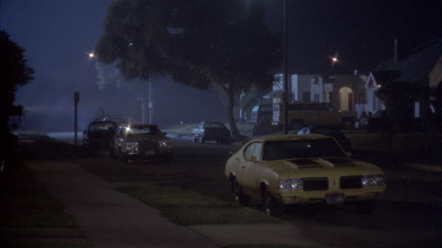 tracking shot of police car driving through residential area. bizbar and flashing lights turn on near middle of shot and police car speeds up. - inglewood video stock e b–roll