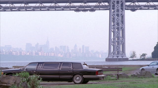 vidéos et rushes de wide angle of black limousine parked by hudson river, george washington bridge, new york city skyline in background. car explode into fireball. fire, flames, and smoke come from limo. explosions. could be car bomb, assasination. - limousine voiture