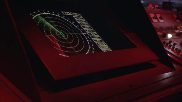 medium angle control panel. see radar screen and graphics. pan right see keyboard, buttons, switches and telephone. see lightning flashes in background. could be  control panel on ship. - schiff stock-videos und b-roll-filmmaterial
