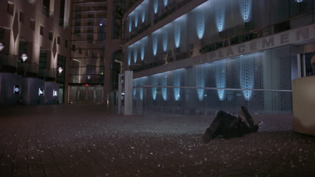 medium angle of stunt man falling from multi-story glass building. see broken glass falling. see man fall to ground of building. see man fall into main hallway or lobby of building. see white and light blue lights along building levels. - 1989 stock videos and b-roll footage