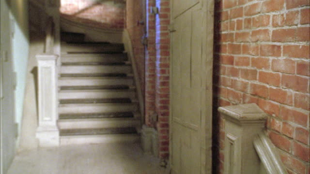 medium angle of grey concrete landing of staircase in loft or apartment building. see brick walls at right and grey door at left. see open faded brown wooden door at right. see patches on sunlight throughout, could be from windows or skylight. - 屋根裏部屋点の映像素材/bロール
