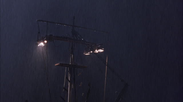 medium angle of boat mast of boat of ship  in the rain. see lights attached overhead on mast that are lit. heavy rain falling down. storms. could be sailboat. oceans. - small boat stock videos & royalty-free footage