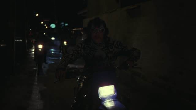 MEDIUM ANGLE, MOVING STRAIGHT BACK POV OF MOTORCYCLE GANG DRIVING UP STREET AND BRIDGE. LEADER IS GROWLING OR SCREAMING MAN WITH METAL FANGS, GOGGLES, DECORATIVE CLOTHING.
