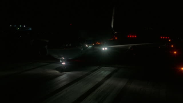 TRACKING SHOT OF AIR FORCE ONE JET DRIVING DOWN RUNWAY TOWARD CAMERA IMMEDIATELY FOLLOWED BY SEVERAL CARS.