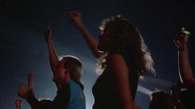 CLOSE UP. SILHOUETTED YOUNG FEMALE ROCK CONCERT AUDIENCE MEMBER DRESSED IN EARLY 1980'S ATTIRE, CHEERING AND DANCING TO MUSIC. SEE OTHER AUDIENCE MEMBERS AROUND HER.
