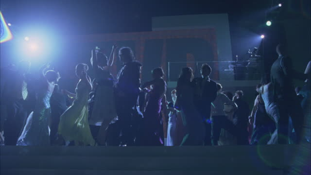 wide angle of teenagers in evening gowns and tuxedos at school dance in ballroom. spotlights. large screen in bg reads vikings fever 4 ever. camera pans around dance floor. could be party or celebration or school dance. - 高校卒業ダンスパーティ点の映像素材/bロール