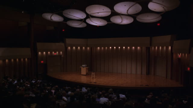 medium angle, auditorium or lecture hall, seats filled with people, stool on lit stage in front. see overhead lights above audience and stage, track lighting on walls. - auditorium stock videos and b-roll footage