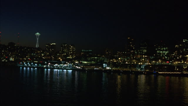 wide angle of seattle skyline at night viewed from puget sound. see the space needle and other skyscrapers or office buildings. building lights are reflected in the water. see traffic lights from cars on freeway or highway along bay.  harbors, bays. - norra stilla havet bildbanksvideor och videomaterial från bakom kulisserna