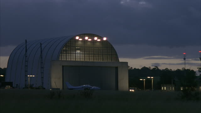 wide angle of hangar in small airport. small airplane in front. car drives across hangar. dark gray clouds. field in foreground and trees in background. - airplane hangar stock videos & royalty-free footage