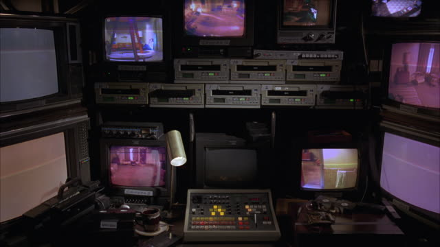 medium angle of several television monitors and videotape recorders in surveillance room. several tv monitors showing video footage of lower class motel room interiors. could be spying, voyeurism. video camera, control panel, switches. - electrical equipment stock videos & royalty-free footage
