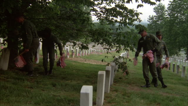 PAN LEFT TO RIGHT OF ARLINGTON NATIONAL CEMETERY. SOLDIERS WALK THROUGH, PLACING AMERICAN FLAGS INTO GROUND IN FRONT OF HEADSTONES, PROBABLY FOR MEMORIAL DAY.