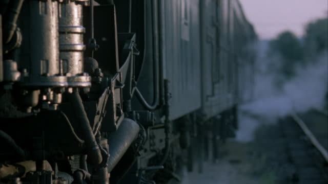 static close up shot of side of steam engine train parked next to a set of railroad tracks, - 1923年点の映像素材/bロール