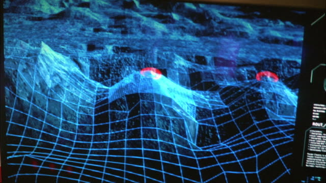 PULL BACK OF BLUE ELECTRONIC MAP SHOWING MOUNTAINS. SEE MAP ZOOM IN ON MOUNTAIN WITH RED SIGNAL. CAMERA PULLS BACK TO SEE CONTROL PERSON RUNNING CONTROL PANEL. COULD BE IN MILITARY CONTROL ROOM. SEE PERSON TALK.