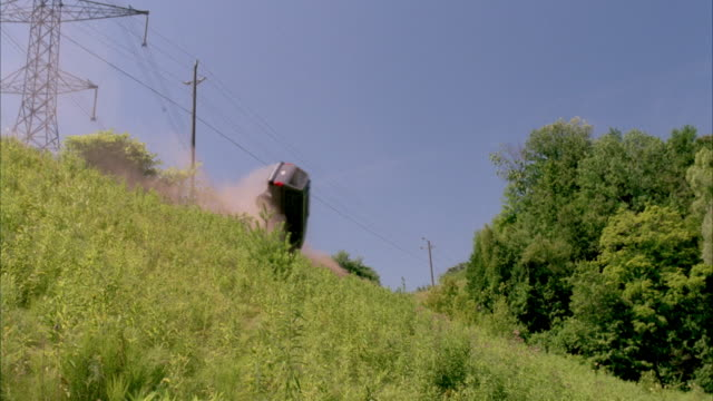 up angle of a white van running off the road above and rolling over and down hillside. see hill covered with grass and trees in background. neg cut. action. - roll over stock videos and b-roll footage