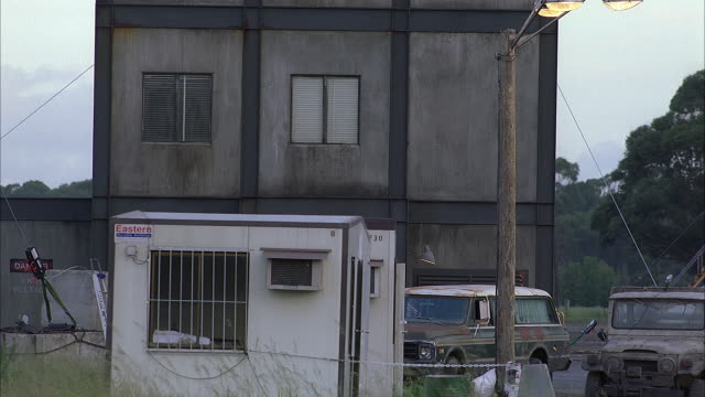 medium angle of two story concrete building with two windows on second floor. see gray metal beams bordering building. see white shack in front of building. see two rusty jeeps in front of building. see old light pole in front of cars. - zweistöckiges bauwerk stock-videos und b-roll-filmmaterial