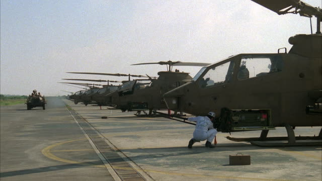 medium angle of cobra military helicopters lined on runway. pilots gets on helicopters and prepare for flight. mechanics converse in front of helicopters. middle east. attack helicopters. - kampfhubschrauber stock-videos und b-roll-filmmaterial