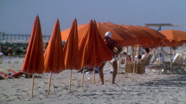 medium angle of man in swimming trunks and hat opens five orange umbrellas on beach. see several others opened in background. see people sitting in beach chairs or lying in sand in background. - parasol stock videos & royalty-free footage