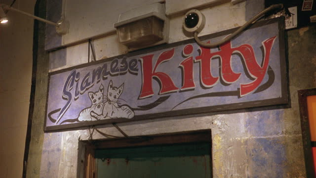 pull back from a door with a sign that reads siamese kitty massage day spa. a security camera over the door. no minors sign on door.  massage parlor or brothel. adult entertainments. lower class. alley. - bordell stock-videos und b-roll-filmmaterial