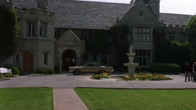 wide angle. est. large stone building in bg. stone driveway with fountain in the middle. grass in fg. vintage green car parked in front. - playboy mansion stock videos & royalty-free footage