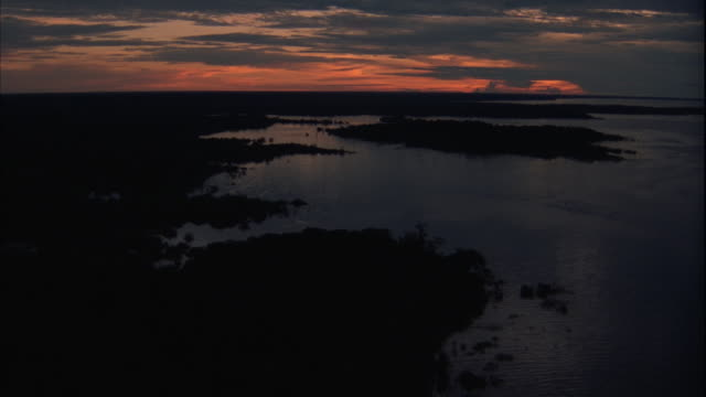 AERIAL OF LARGE RIVER BASIN ON COASTLINE OF RAINFOREST. SWAMP OR MARSH ON SHORE. ORANGE SKY AND SOME CLOUDS IN BACKGROUND. ZOOMS IN SLIGHTLY AT END.