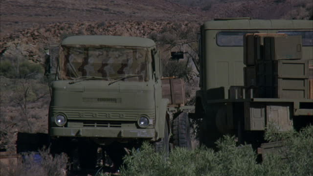 vidéos et rushes de medium angle of two old military trucks in arid or desert area. see green and wood boxes in bed of right truck. see desert shrubs. explosion. - véhicule militaire terrestre
