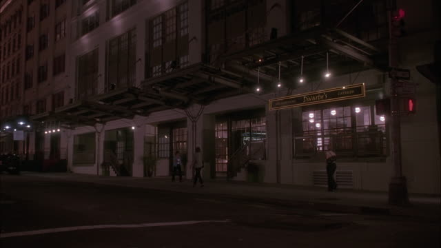 wide angle of multi-story building from pov across street on ground level. see lit up windows. could be apartment of office building. pedestrians walking on sidewalk in front of building. - level stock videos and b-roll footage