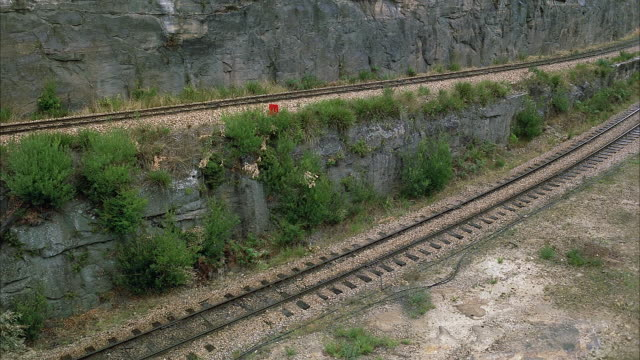 MEDIUM ANGLE OF SPLIT RAILROAD TRACKS. SEE ONE TRACK RISE ALONG HIGHER SLOPE OF ROCKY MOUNTAINSIDE WALL. SEE SECOND TRACK CURVE DOWNWARDS TO BOTTOM LEFT ALONG DIRT SLOPE. SEE GREEN SHRUBS THROUGHOUT.