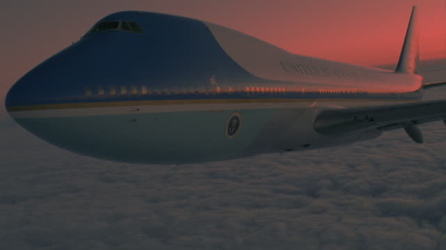 MEDIUM 3/4 FRONT ANGLE OF AIR FORCE ONE FLYING OVER LAYER OF WHITE CLOUDS IN SKY. SEE HORIZON OF CLOUDS AND SKY WITH TINT OF RED.