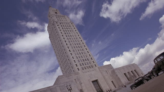 wide angle of the louisiana capitol building in baton rouge.  a dutch angle of the art deco building against the partly cloudy sky. - kapitol von louisiana stock-videos und b-roll-filmmaterial