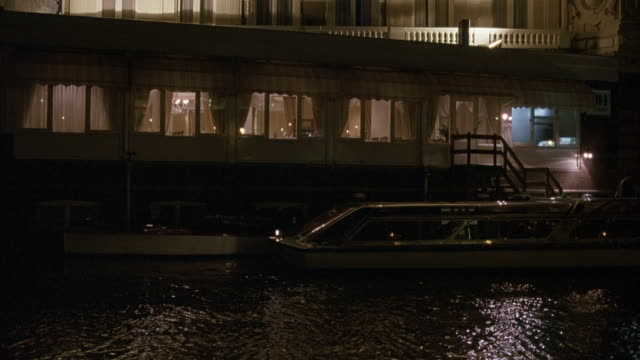 wide angle of ferry parked in front of waterfront building.  amsterdam canals. could be hotel or restaurant. night. - ferry stock videos and b-roll footage