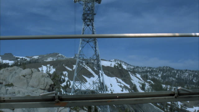 wide angle, moving pov of view from inside gondola of aerial cable car approaching mountain terminal or ski lodge. gondola safety bar in foreground. snowy mountain, and cables hanging in background. cable towers visible. neg cut. - ski lodge stock videos & royalty-free footage