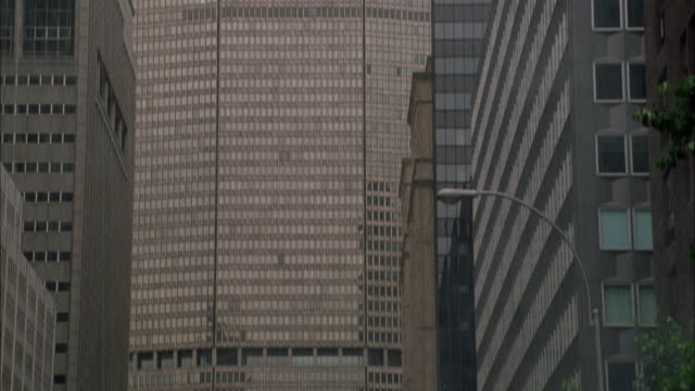 stockvideo's en b-roll-footage met pan down from top of metlife office building to soldiers running down middle of street below. soldiers are looking up to top of building while one soldier is talking on portable backpack radio. see rain pouring down. - metlife building