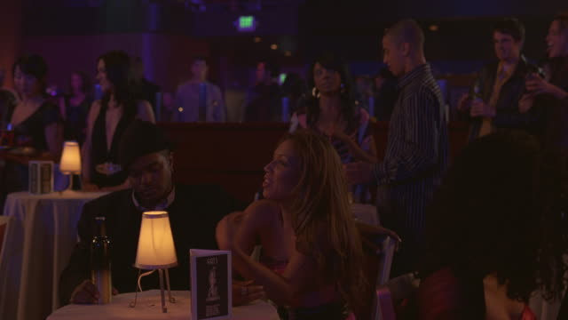 WIDE ANGLE OF CLUB CROWD IN THEATER OR NIGHT CLUB. COUPLE SITS AT ONE OF SMALL TABLES IN FG AND TALKS. OTHERS IN BG NOD THEIR HEADS, DANCE TO MUSIC, AND MINGLE.