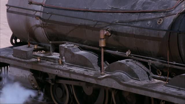 medium angle of steam engine train wheels and train tracks. see steam escaping from beneath locomotive. camera zooms out to engine top. see coal and train conductors operating train controls. see train traveling right to left across desert landscape. - locomotive stock-videos und b-roll-filmmaterial