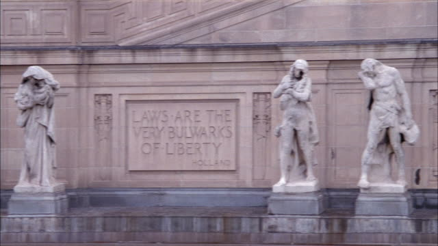 vidéos et rushes de close angle of top of stone courthouse or government building. see stone carvings or carved reliefs and statues along top front of building. - pont longfellow