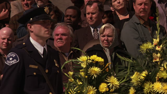 close angle of mourners at state funeral in front of capitol building in baton rouge, louisiana. mourners, police officer in period costume, flowers. could be used for parade crowd. - kapitol von louisiana stock-videos und b-roll-filmmaterial