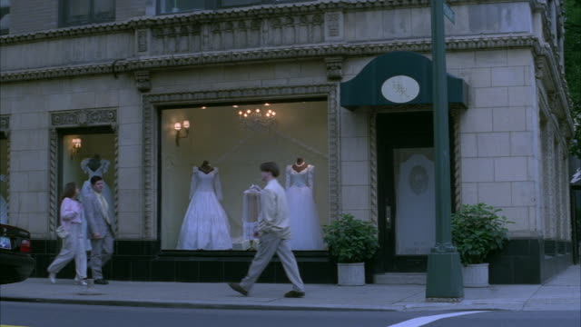 MEDIUM ANGLE OF STOREFRONT OF WEDDING SHOP WITH FOUR WEDDING DRESSES ON DISPLAY. STORE ON STREET CORNER, SIDEWALK AND STREET IN FOREGROUND. PEDESTRIANS AND CARS PASS IN FRONT.