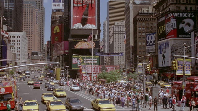 vídeos y material grabado en eventos de stock de wide angle of times square with crowd and taxis on streets. pans up along building with neon signs of different companies, coke, suntory, samsung, and mtv. - 1996
