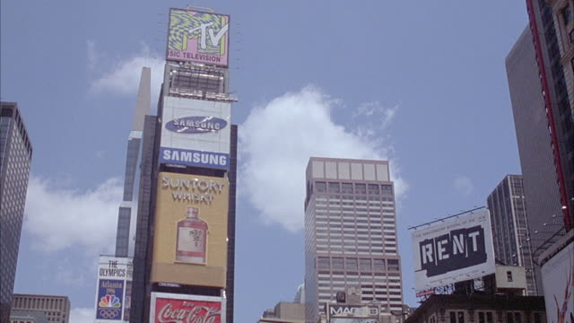 WIDE ANGLE OF TIMES SQUARE WITH  BUILDING WITH NEON SIGNS OF DIFFERENT COMPANIES, MTV, SAMSUNG, SUNTORY, AND COKE. PANS DOWN TO CROWD AND TAXIS ON STREETS.