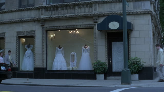 medium angle of storefront of wedding shop with four wedding dresses on display. store on street corner, sidewalk and street in foreground. pedestrians and cars pass in front. - wedding dress stock videos and b-roll footage