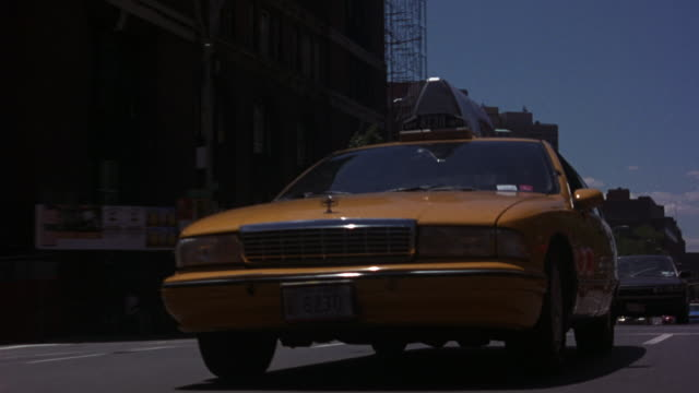 medium angle moving pov of cars driving along new york city street. focus on yellow taxi cab as it speeds up at left. see taxi slow to drop behind red four door passenger car at right. repeat. - yellow taxi bildbanksvideor och videomaterial från bakom kulisserna