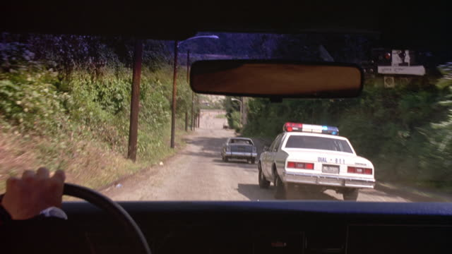 MEDIUM ANGLE OF POLICE CARS FOLLOWING BLUE FORD CROWN VICTORIA DOWN SMALL SIDE STREET. POV IS THROUGH FRONT WINDSHIELD FROM INSIDE CAR. SEE HAND GUIDING STEERING WHEEL.