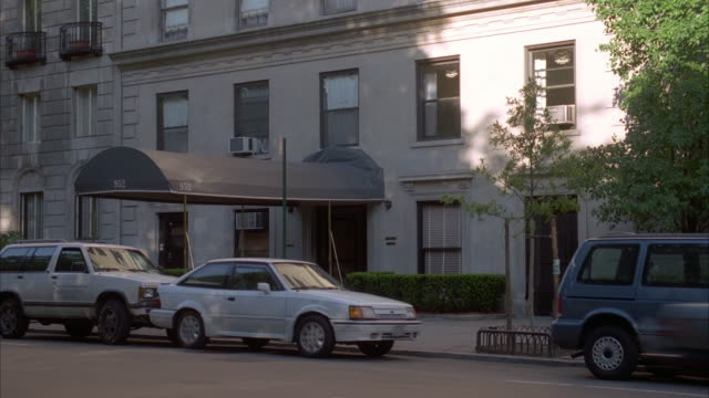 MEDIUM ANGLE OF WHITE BUILDING WITH SMALL AWNING OVER ENTRANCE. COULD BE APARTMENT BUILDING OR HOTEL. WHITE SUV BUMPS INTO WHITE CAR AND MOVES IT FORWARD