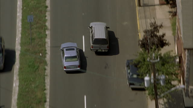 aerial tracking shot of silver mercedes down street in urban area as it weaves through traffic. see car cross under several freeway overpasses. neg cut. - mercedes benz stock videos and b-roll footage