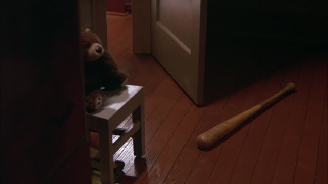 CLOSE ANGLE OF HARDWOOD FLOOR WITH BASEBALL BAT, STUFFED ANIMAL OR TEDDY BEAR SITTING IN MINIATURE CHAIR AND OPENED DOOR. COULD BE ROOM OF KID OR CHILD.