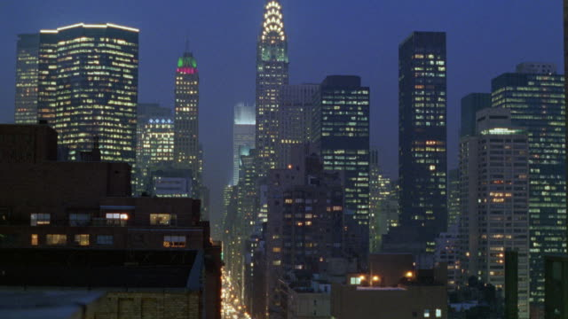wide angle of new york city skyline. see office lights from buildings and headlights from cars below. - 1995年点の映像素材/bロール