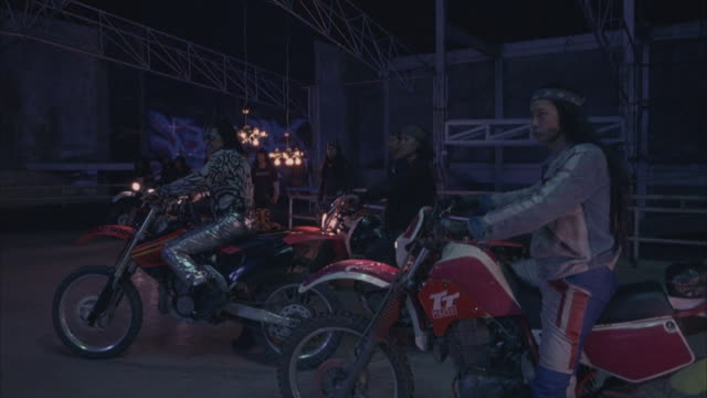 wide angle of industrial building interior with modern chairs. gang of men on motorcycles arrives, leader screams. - biker gang stock videos & royalty-free footage
